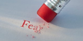 Studio shot of pencil erasing the word fear from piece of paper